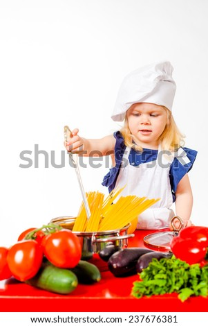 Cute girl in white cap cook standing beside wooden table with pan - stock photo
