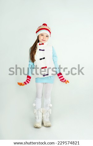 Cute girl in winter clothes with a white blank paper sheet. Christmas, x-mas, people, advertisement, sale concept. Facial expressions. - stock photo