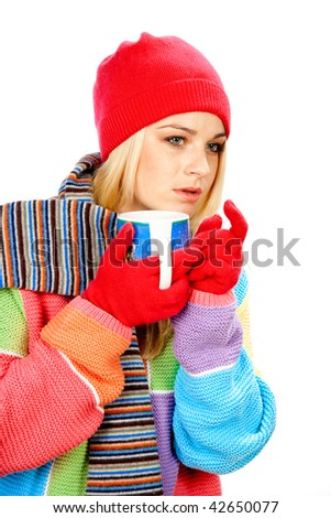 Cute girl in winter clothes with cup of hot drink looking for someone - stock photo
