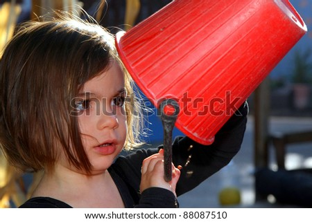 Cute girl inspecting contents of bucket - stock photo