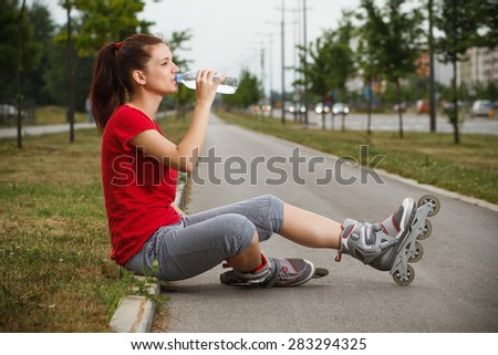 Cute girl is drinking water and resting after roller skating.Refreshment after roller skating - stock photo