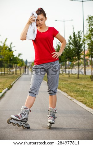 Cute girl is resting after roller skating.Exhaustion after roller skating - stock photo