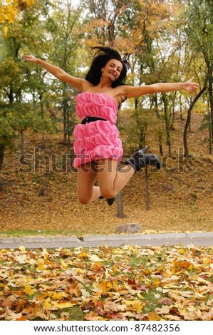 cute girl jumping at an autumn park