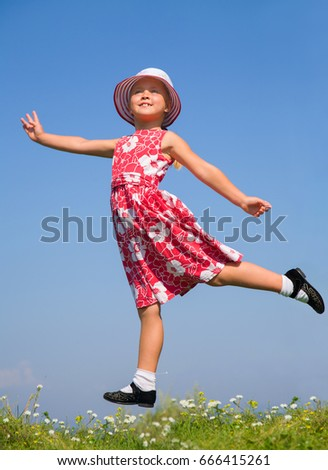 Cute girl jumping on summer meadow against blue sky