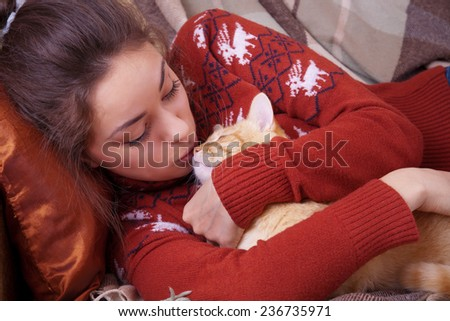 Cute girl kisses a red cat on the nose - stock photo