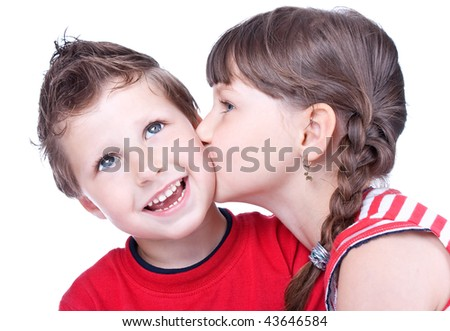 Cute girl kissing a blue eyed boy, studio shot