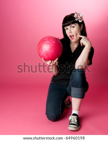 Cute girl kneeling on one knee holding a bowling ball - stock photo