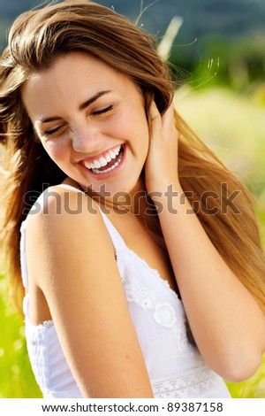cute girl laughs with joy outdoors in the sunlight - stock photo