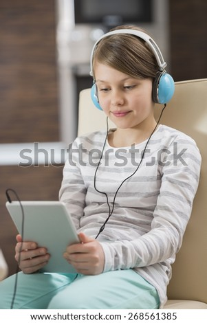 Cute girl listening music while using digital tablet at home - stock photo