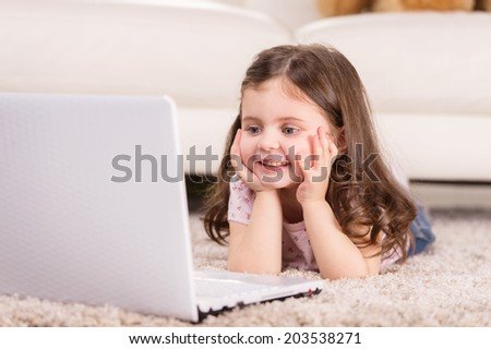 Cute girl looking at screen of computer. nice girl lying on floor and smiling  - stock photo