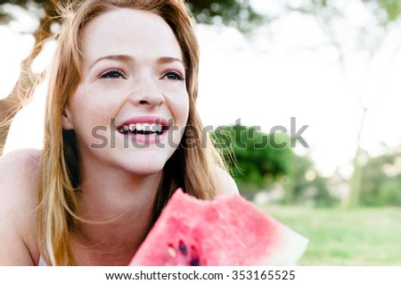 Cute girl lying down and eating slice of juicy red watermelon outdoors in park, lots of copy space - stock photo