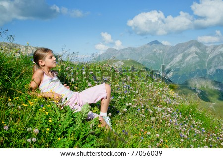 Cute girl lying in a meadow background Alps