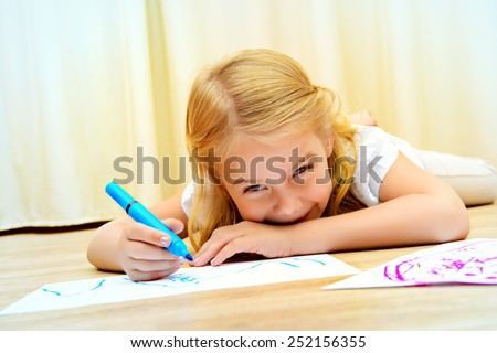 Cute girl lying on a floor and drawing on paper with colorful pens. - stock photo