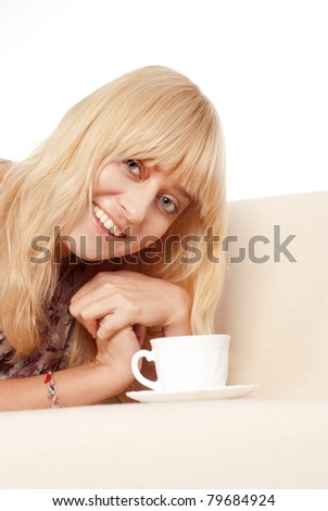 cute girl lying on a sofa with cup