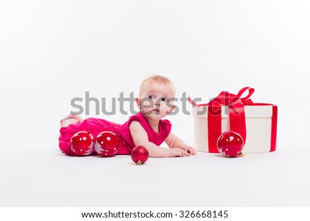 Cute girl lying on her stomach on a white background in a smart red dress among red Christmas balls and red boxes with gifts, picture with depth of field - stock photo