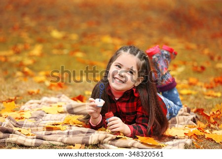 Cute girl lying on plaid and blowing soap bubbles in park
