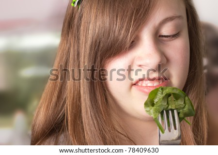 Cute girl making a disgusted face while eating greens - stock photo