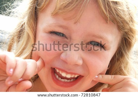 Cute girl making a funny smiling face for the camera.