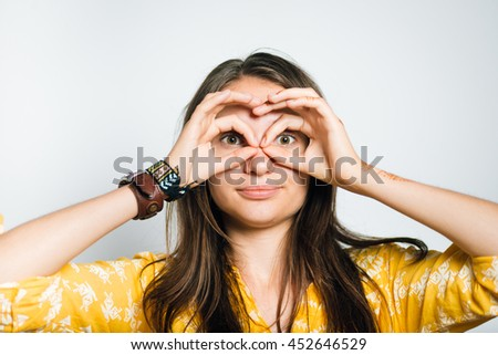 cute girl making binoculars hands, isolated on a gray background