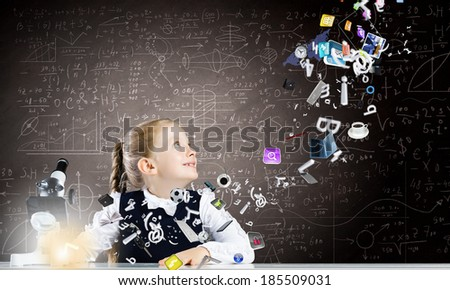 Cute girl of school age using microscope. Technology concept - stock photo