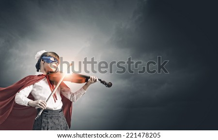 Cute girl of school in superhero costume playing violin - stock photo