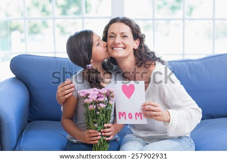Cute girl offering flowers and card to her mother in the living room - stock photo