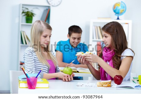Cute girl offering her friend sandwich during break in college