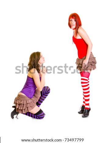 Cute girl on knees beging her shocked girlfriend isolated on white - stock photo