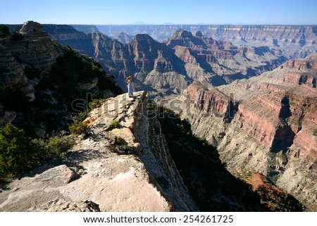 Cute girl  on the edge of picturesque cliffs of The Grand Canyon - stock photo