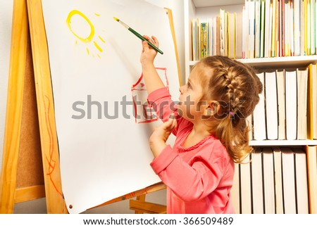 Cute girl painting brush watercolors on a easel - stock photo