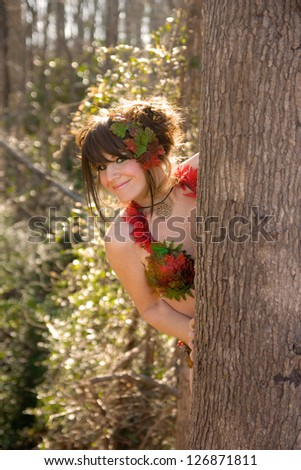 Cute Girl Peeking From Behind Tree and Smiling - stock photo