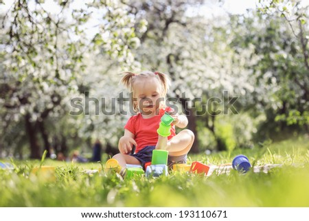 Cute girl plaing in the park on a summer day - stock photo