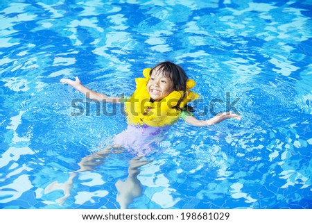 Cute girl playful on the pool while wearing a life jacket. - stock photo