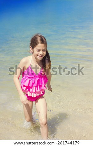 Cute Girl Playing in the Ocean water on Vacation