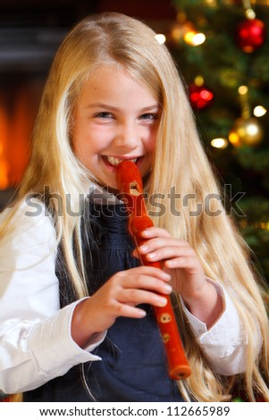 cute girl playing recorder on christmas eve