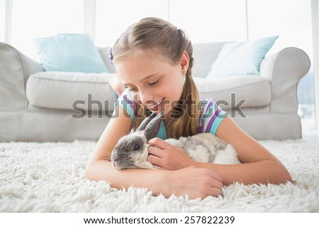 Cute girl playing with rabbit while lying on rug in living room - stock photo