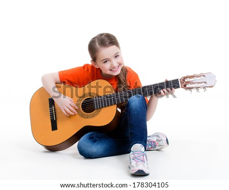 Cute girl plays on the acoustic guitar with bright emotions -  isolated on white background. - stock photo