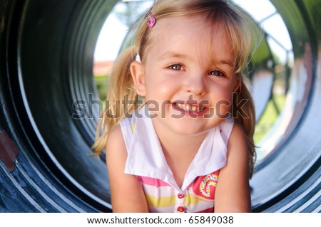 Cute girl poses in tunnel at the playground - stock photo
