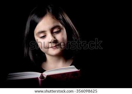 Cute girl posing on a black background while reading - stock photo