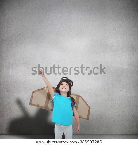 Cute girl pretending to be pilot against grey room - stock photo
