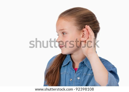 Cute girl pricking up her ear against a white background - stock photo