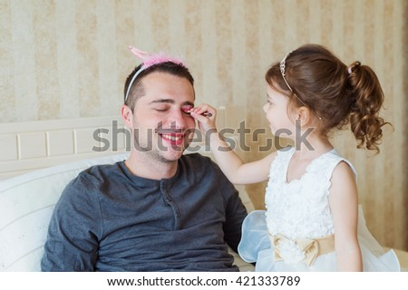 Cute girl putting on make up on her father. Young father enjoying time with child. Fathers day with daughter at home. Handsome father with little girl. Happy father and daughter. - stock photo