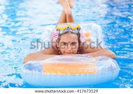 Cute girl relaxing in pool - stock photo