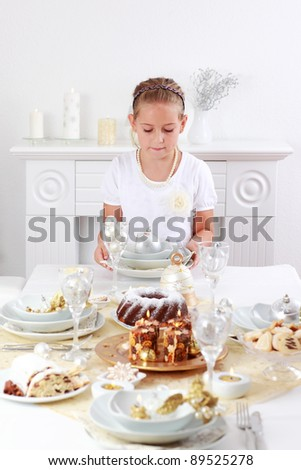 Cute girl setting table for Christmas - stock photo