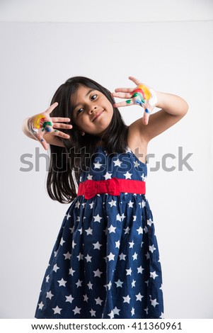 cute girl showing her colorful hands, surprised. Indian young girl with palm painted, asian girl and palm painting, palm printing - stock photo