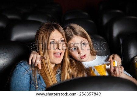 Cute girl showing something to shocked mother while watching movie in cinema theater - stock photo