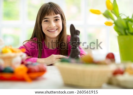 Cute girl sit for Easter decorated table, smiling and looking at camera - stock photo