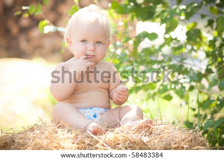 cute girl sitting on a large hay bale under the tree - stock photo