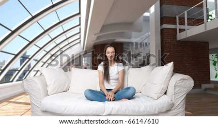 Cute girl sitting on a sofa in a magnificent luxurious loft - stock photo
