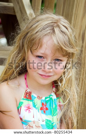 Cute girl sitting on deck steps outside.